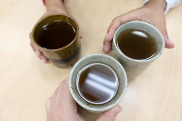 Three Multi-Ethnic People Toasting Ceramic Hot Brown Tea Mugs