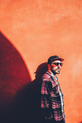 Bearded man in cap and sunglasses on red wall in sunlight