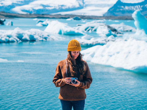 Hipster woman holding a camera in a glacier lake