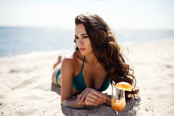 Attractive young woman with long wavy hair in blue bikini on beach with exotic cocktail against of seascape.