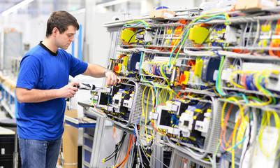 Elektroniker montiert eine Maschine in einer Fabrik // electronics mounted a machine in a factory