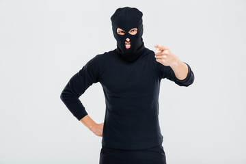 Mad irritated man in balaclava standing and pointing on you