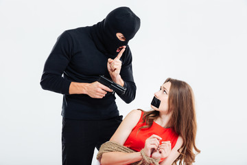 Man threatening by gun and showing silence gesture to woman