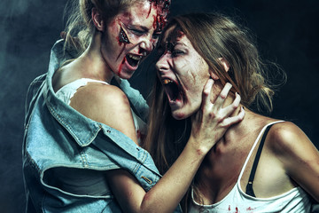 Horror zombies fighting with woman. Close-up portrait of horrible vampire girl. Halloween holiday.
