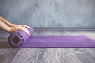 Canvas Prints Yoga school Woman rolling her mat after a yoga class
