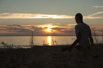 Silhouette of young man practicing yoga on beach