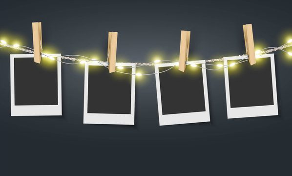 Blank photo frame hanging on rope with fairy lights Vector