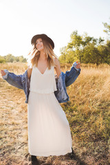 Beautiful blonde woman in a long white dress, denim jacket and hat posing in the field. Boho style