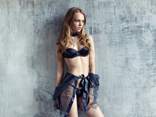 Beautiful blond model wearing sexy lingerie posing against gray concrete wall.