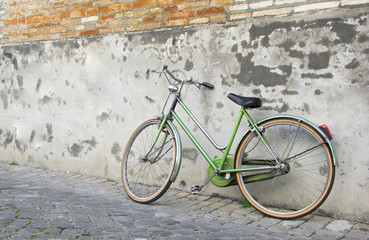 Green Old retro bicycle leaning against a wall