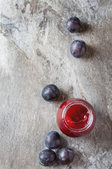 Homemade jam of plums with cinnamon and fresh fruits on gray sto