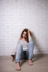 sad woman sitting on the floor, crying and drinking wine