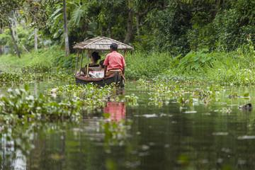 Unidentified indian people in small boat in Kerala backwaters.