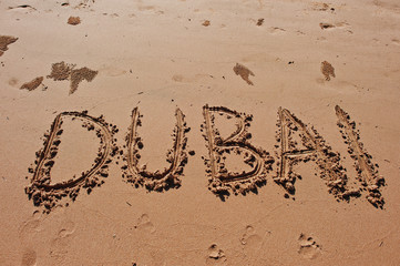 """Dubai"" written in the sand on the beach"