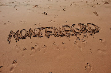 """Montenegro"" written in the sand on the beach"