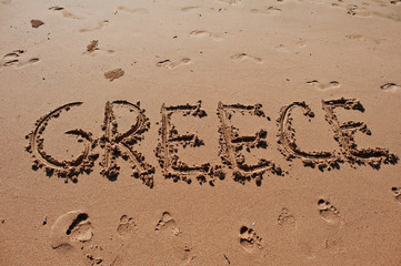 """Greece"" written in the sand on the beach"