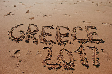 """Greece 2017"" written in the sand on the beach"