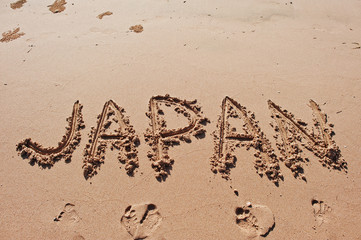 """Japan"" written in the sand on the beach"