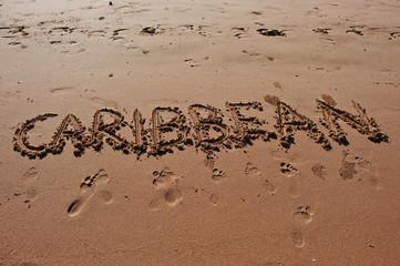 """Caribbean"" written in the sand on the beach"
