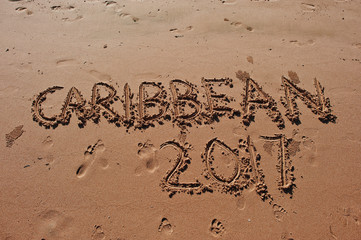 """Caribbean 2017"" written in the sand on the beach"