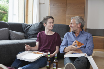 Father and son sitting on the floor eating pizza in living room