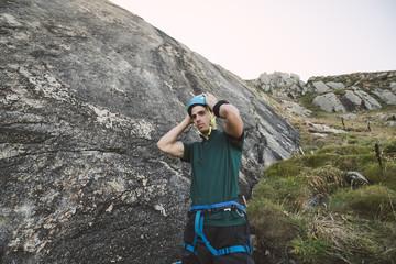 Young man putting on climbing helmet