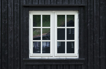 Colonial style casement window of white painted wood in a black tongue and groove plank facade