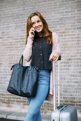 Smiling young woman with wheeled luggage and leather bag on the phone