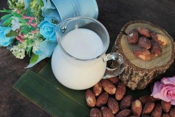 Almond milk with almond on wood background.