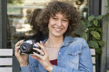 Portrait of smiling young woman with old camera sitting in a sidewalk cafe