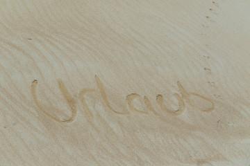 ein in den Sand gezeichnetem  Wort in Deutsch Urlaub.
