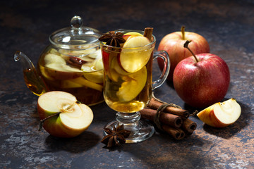 glass of hot apple tea with spices on dark table, closeup