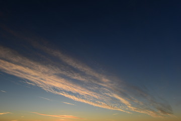 Blue sky with white stripe clouds in the sunset light
