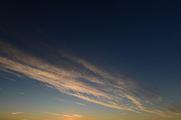 Clouds white stripe in the clear blue autumn sky at sunset