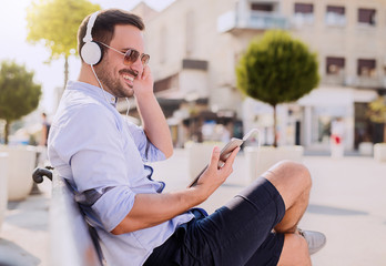Man using tablet / Young smiling man sitting on the bench somewhere in the city and looking at tablet, he listening to music