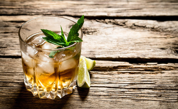 glass of rum with ice , lime and mint.