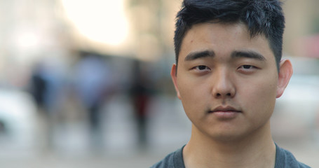 Young Asian man in city face portrait