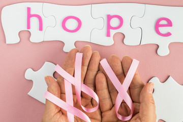 Woman hands holding breast cancer awareness pink ribbon.