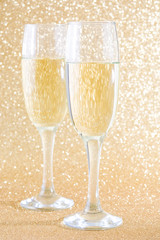 Champagne glass cups on brilliant golden background