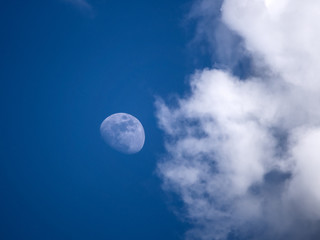 Moon with clouds on blue sky during daylight
