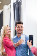 Young Couple Taking Selfie Photo Fitting Room Fashion Shop, Happy Smiling Man And Woman Shopping Customers Trying Clothes