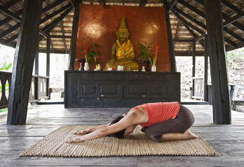 Women practicing yoga in a traditional Thai house