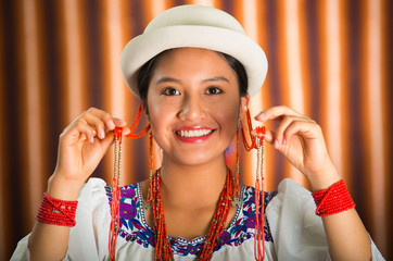 Bautiful hispanic model wearing andean traditional clothing with matching white hat, smiling and interacting using hands for camera, beige studio curtain background