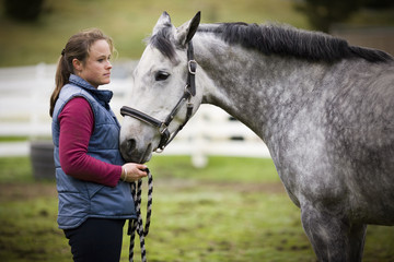 Young woman standing with her grey horse in a paddock.