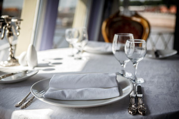 Serving of the dinner table in the cabin restaurant ocean ship. The food and service at the marine ship. Utensils for passenger cruises.