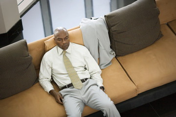 Unhappy businessman sitting alone on a couch.