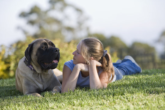 Teenage girl sitting with her dog in the garden.