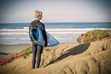 Young man wearing a wetsuit and holding a surfboard while standing on a remote beach.