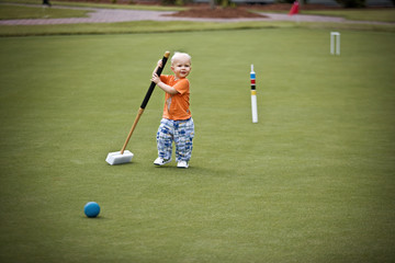 Male toddler attempting to play croquet