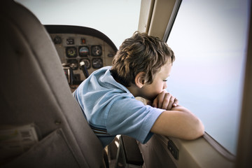 Boy looking out while traveling by plane